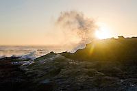 A large wave crashes over rocks along the California Coast at sunset.