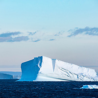 A wedge-shaped iceberg floats in thee Orleans Strait, Palmer Archipelago, Antarctica.