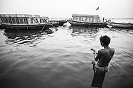 Varanasi, A hindu man offers puja on the Ganges. Rendered in a sepia and purple split-tone.