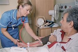 Staff nurse on medical ward taking patient's blood pressure,