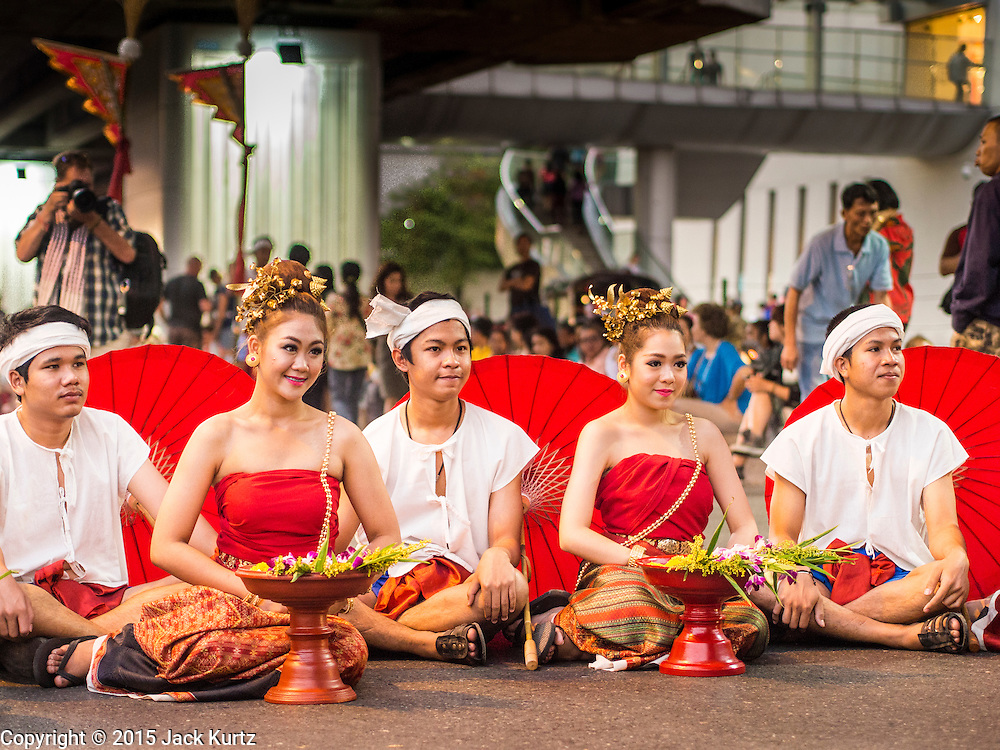 """14 JANUARY 2015 - BANGKOK, THAILAND:  People participating in the 2015 Discover Thainess parade take a break during the parade. The Tourism Authority of Thailand (TAT) sponsored the opening ceremony of the """"2015 Discover Thainess"""" Campaign with a 3.5-kilometre parade through central Bangkok. The parade featured cultural shows from several parts of Thailand. Part of the """"2015 Discover Thainess"""" campaign is a showcase of Thailand's culture and natural heritage and is divided into five categories that match the major regions of Thailand – Central Region, North, Northeast, East and South.    PHOTO BY JACK KURTZ"""