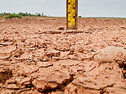 08 APRIL 2010 - NAKHON PHANOM, THAILAND: Dry earth and a dry depth gauge in the bottom of Hua Hin Sanon reservoir in Nakhon Phanom province, Thailand. The 600 acre reservoir was built in 1985 and this the first year it's been empty. The region is in the midst of a record setting drought and the Mekong River is at its lowest point in nearly 50 years, setting up an environmental disaster the region has never seen before. Many of the people who live along the river farm and fish. They claim their crops yields are greatly reduced and that many days they return from fishing with empty nets. The river is so shallow now that fisherman who used to go out in boats now work from the banks and sandbars on foot or wade into the river. In addition to low river levels the Isan region of Thailand is also in the midst of a record drought and heat wave. Farmers have been encouraged to switch from rice to less water intensive crops and to expect lower yields. Farmers here rely more on rain fall than irrigation to water their crops.       PHOTO BY JACK KURTZ