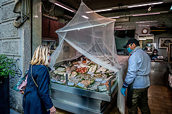 Fish shop uses a mosquito net to protect the fish from the virus in Milan, Italy on April 18, 2020. Daily life scenes with the new anti-COVID-19 Coronavirus prevention measures. Photo by Carlo Cozzoli/IPA/ABACAPRESS.COM