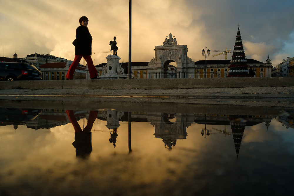 A lady passes by Terreiro do Paço, also know as Praça do Comércio (Commerce Square). This square is the largest in Lisbon and is located just by the river Tagus. From left to right can be seen Augusta Street Arch and the equestrian statue of King Joseph I.