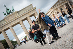16 September 2021, Berlin, Germany: A group of tourists take a group selfie at the historical site of Brandenburger Tor in Berlin.