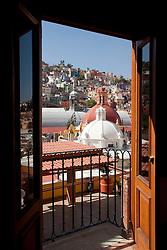North America, Mexico, Guanajuato State, Guanajuato, church cupolas and colorful houses on hillside, viewed through hotel room doors.  Guanajuato is UNESCO World Heritage Site.  PR