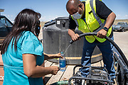 Aaron Wood, volunteer with Water Warriors, gives the remaining drips of water to Renee Shorty after filling a residents' barrel in the White Rock Chapter of the Navajo Nation.