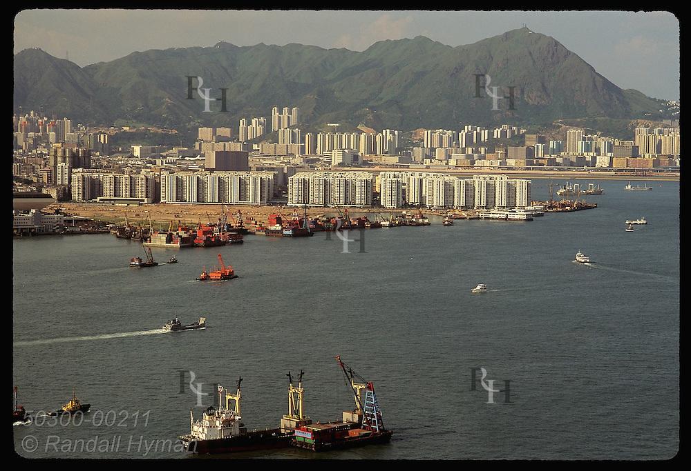 High-rise apartments crowd land between Kowloon's rocky hills and Hong Kong's busy harbor; aerial. Hong Kong