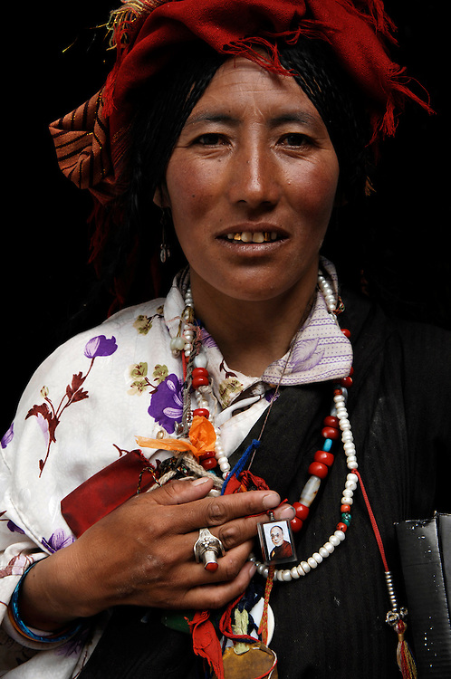 A pilgrim to the Jokhang Temple proudly reveals a portrait of HH The Dalai Lama, hanging around her neck. The Chinese are prone to arrest Tibetans for such actions.