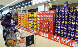 © Licensed to London News Pictures. 08/04/2020. London, UK. A woman wearing a face mask walks past a wide range of Easter Eggs at Sainsbury's supermarket in north London. The supermarket has lifted restrictions on Easter Eggs during COVID 19 outbreak. Photo credit: Dinendra Haria/LNP