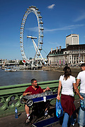 Tourists cross Westminster bridge by the River Thames at Westminter, London and listen to a busker playing empty glasses. With the iconic London Eye behind this is one of the busiest areas for tourism in the city.