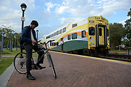 A bicyclist waits to board a SunRail commuter passenger train as it arrives at a station in Winter Park, Fla., Wednesday, Oct. 28, 2015. (Phelan M. Ebenhack via AP)