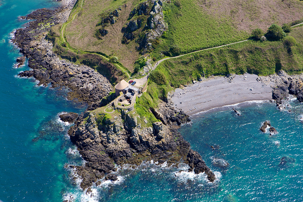 Aerial view of the Heritage property La Crete Fort on the edge of a cliff, surrounded by calm, crystal clear water at Bonne Nuit, Jersey, Channel Islands