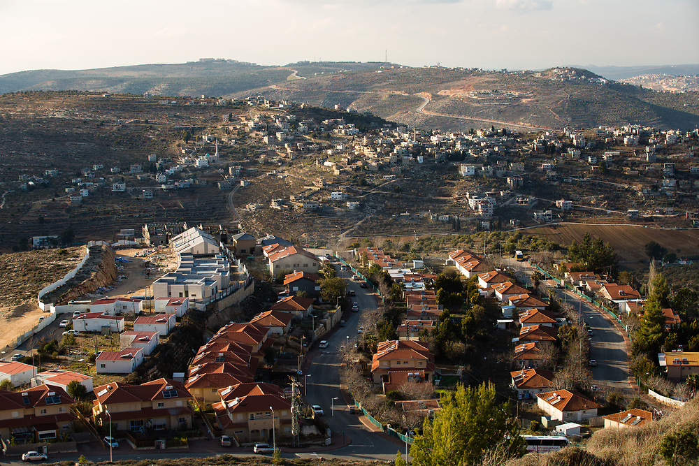 A Palestinian village is seen in the background behind houses at the West Bank Jewish settlement of Eli, located south of the Palestinian West Bank town of Nablus, on January 1, 2017.