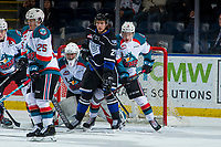 KELOWNA, CANADA - JANUARY 25: Phillip Schultz #27 of the Victoria Royals is stick checked by Lassi Thomson #2 in front of the net of James Porter #1 of the Kelowna Rockets  on January 25, 2019 at Prospera Place in Kelowna, British Columbia, Canada.  (Photo by Marissa Baecker/Shoot the Breeze)
