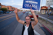 02 OCTOBER 2008 -- PHOENIX, AZ: RON BOWEN, a veterans' outreach worker and member of Veterans for Obama, waves at motorists on a Phoenix street before the Vice Presidential debate Thursday night. About 200 people, mostly supporters of Democratic Presidential candidate Barack Obama gathered in a vacant lot in Phoenix in 100 degree heat to watch Vice Presidential debate between Gov. Sarah Palin and Sen. Joe Biden. Photo by Jack Kurtz
