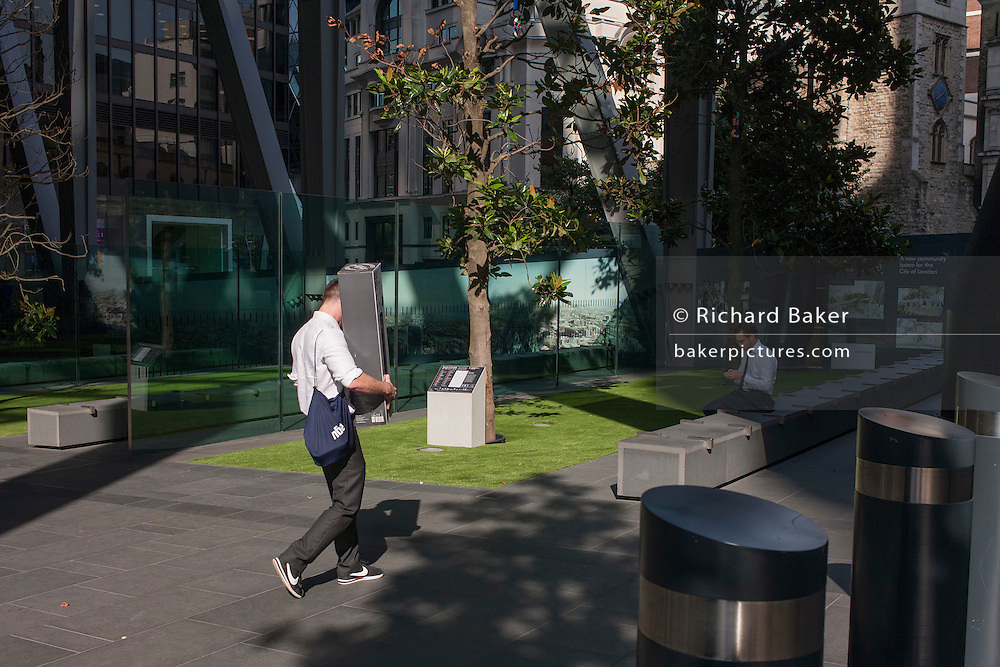 """A man carries an itembeneath the tall supports at 122 Leadenhall Street, or the Leadenhall Building, a 225 m (737 ft) tall building on Leadenhall Street in the City of London UK. The commercial skyscraper, opened in July 2014, was designed by Rogers Stirk Harbour + Partners and is informally known as """"The Cheesegrater"""" because of its distinctive wedge shape"""