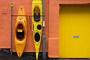 Kayaks and canoes stand upright against a shop wall in Oban, Scotland. With a background of orange render and a yellow door to this outdoor adventure shop, the two coastal sport boats combine perfectly with the echoed colours, similar pastel colours on the spectrum. In addition, we see a yellow At Any Time street sign preventing motorists from parking here at the roadside. We are in a back street of Oban, a west coast ferry town that serves many outlying isles in this wild region of Scotland. Visitors enjoy sea kayaking which can be expensive to hire so these two examples can be bought from the outfitters for around £700 and £1,00 respectively. Interestingly, the brand for the smaller boat is Eskimo, a term seen in some regions of north America as unacceptable, while in others used more widely.