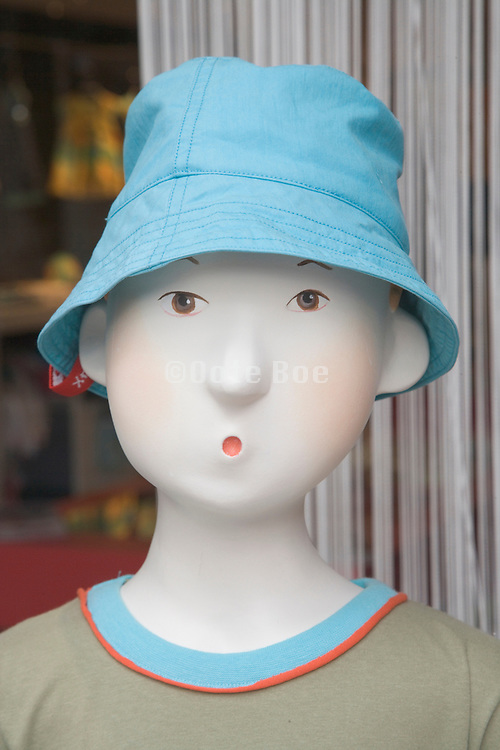portrait of a boy mannequin in a clothing shop window
