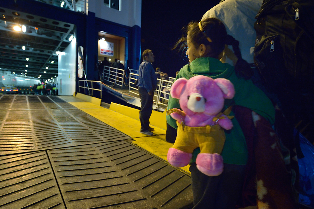 Her stuffed bear on her back, a refugee girl watches as a ferry docks at night on the Greek island of Chios. She and her family came to the island by crossing the Aegean Sea on a small boat from Turkey. Upon arrival, they were registered and provided with food and shelter in a reception center built with support from International Orthodox Christian Charities, a member of the ACT Alliance. Now she and her family are moving on to Athens, and from there on to western Europe. Hundreds of thousands of refugees and migrants have passed through Greece in 2015. <br /> <br /> Parental consent obtained.