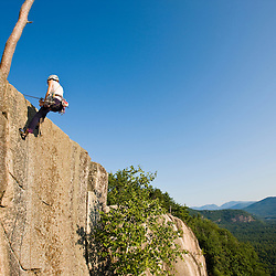 A woman rappels from the top of Cathedral Ledge.  Echo Lake State Park in North Conway, New Hampshire.  White Mountains.