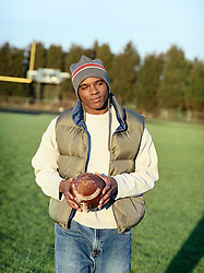 Good looking man in a winter hat and vest holding a football on a football field