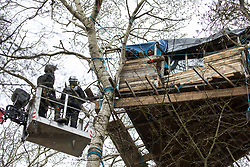 Steeple Claydon, UK. 23 February, 2021. Anti-HS2 activists observe National Eviction Team bailiffs in a cherry picker from a tree house during an operation by HS2 Ltd to evict activists living in ancient woodland known as Poors Piece. The activists created the Poors Piece Conservation Project there in spring 2020 after having been invited to stay on the land by its owner, farmer Clive Higgins. Already, local village communities have been hugely impacted by HS2, with 550 acres of land seized including a large section of a nature reserve.