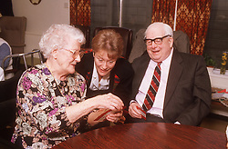 Elderly man and woman playing game of cards at day centre with carer watching,