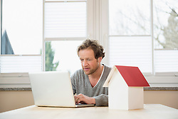 Man with architectural model and laptop at table