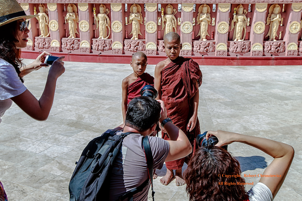 Young and Patient:  Two young Buddhist monks humour tourists and practiced both their patience and understanding; as they pose for foreigners of various ethnic origins, each with expensive camera equipment, Sitagu International Buddhist University, Sagaing-Mandalay, Myanmar.