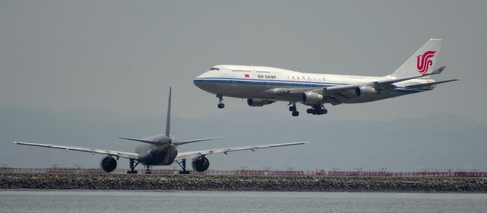 Air China commercial passanger Boeing 747-400 jumbo jet plane landing on runway at San Francisco Int'l Airport, California