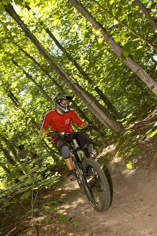 A mountain biker navigates a wooded trail while freeriding near Marquette, Michigan.