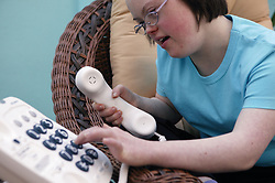Teenage Downs Syndrome girl using a large button telephone,
