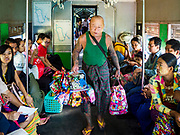 25 NOVEMBER 2017 - YANGON, MYANMAR: A toy vendor on the Yangon Circular Train. The Yangon Circular Train is a 45.9-kilometre (28.5 mi) 39-station two track loop system connects satellite towns and suburban areas to downtown. The train was built during the British colonial period, the second track was built in 1954. Trains currently run both directions (clockwise and counter-clockwise) around the city. The trains are the least expensive way to get across Yangon and they are very popular with Yangon's working class. About 100,000 people ride the train every day. A a ticket costs 200 Kyat (about .17¢ US) for the entire 28.5 mile loop.     PHOTO BY JACK KURTZ