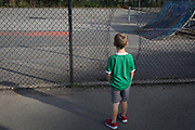 An eight year-old boy decides whether to climb through a hole in fencing to a tennis court, on 25th August, in Ruskin Park, London borough of Lambeth, England.