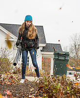 Jillian Palisi cleans out the front gardens at the Gilford Community Center during Gilford/Gilmanton Community Service Day on Tuesday.  (Karen Bobotas/for the Laconia Daily Sun)