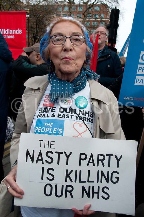 Tens of thousands of health workers, activists and members of the public protested against austerity and cuts in the NHS National Health Service on March 4th 2017 in London, United Kingdom. A woman holds a sign saying The nasty party is killing our NHS a reference to Theresa May calling the conservatives the nasty party. She is wearing a t shirt which says Save our NHS, Hull and East Yorks.