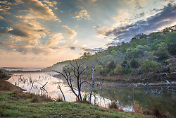 Spring-fed pond and landscape at sunrise, Hill Country between Blanco and Fredericksburg, Texas, USA