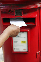 Close up of a letter being posted in to a post box,