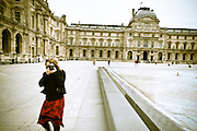 Stock / American woman tourist standing in front of the Louvre, taking a photograph.