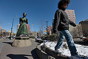 A boy walks by the statue dedicated to African-American abolitionist Harriet Tubman located on St. Nicholas Avenue in Harlem.  Harlem, a neighborhood of New York City in Manhattan, began as a Dutch village in 1658 and was later annexed to New York City in 1873.  At the beginning of the 20th century African-American's began arriving from the southern American states looking for work in the more industrious north.  With their migration, the African-American community brought with them a renaissance in the arts to Harlem that is still evident today.  After World War II Harlem began experiencing a significant rise in crime and poverty due to the Great Depression that lasted until the 21st century.  A new pride in the community has brought a renewed revival to Harlem, and crime rates have dropped to record lows giving the New York City neighborhood a new lease on life.