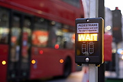 The 'Wait' sign is illuminated while a London bus passes a crossing at the top of Ludgate Hill in the City of London, on 26th February 2021, in London, England.