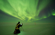 An oilfield worker takes a photograph of the aurora borealis as it dances in the sky above the ice road at Alpine Oilfield on Alaska's north slope.
