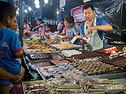 16 NOVEMBER 2013 - BANGKOK, THAILAND: A food vendor sells Thai snacks at the Wat Saket Temple Fair. Wat Saket is on a man-made hill in the historic section of Bangkok. The temple has golden spire that is 260 feet high which was the highest point in Bangkok for more than 100 years. The temple construction began in the 1800s in the reign of King Rama III and was completed in the reign of King Rama IV. The annual temple fair is held on the 12th lunar month, for nine days around the November full moon. During the fair a red cloth (reminiscent of a monk's robe) is placed around the Golden Mount while the temple grounds hosts Thai traditional theatre, food stalls and traditional shows.    PHOTO BY JACK KURTZ