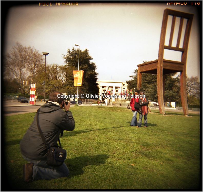 Switzerland. Geneva. Tourists photograph on the place of Nations in front of the chair with the broken foot representing a symbol of the fight(against the antipersonal mines. Behind the siege of United Nations in Geneva.
