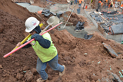 Laborer in motion carries shovel and rake up grade. Central Connecticut State University. New Academic / Office Building. Project No: BI-RC-324. Architect: Burt Hill Kosar Rittelmann Associates . Contractor: Gilbane Building Company, Glastonbury, CT.