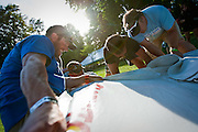 Mac Brown, left, with WTC Ironman, gives a firm pull to dismantle the tarp of the Newton Running shoe company tent in City Park Saturday evening in preparation for Sunday's Ford Ironman competition.