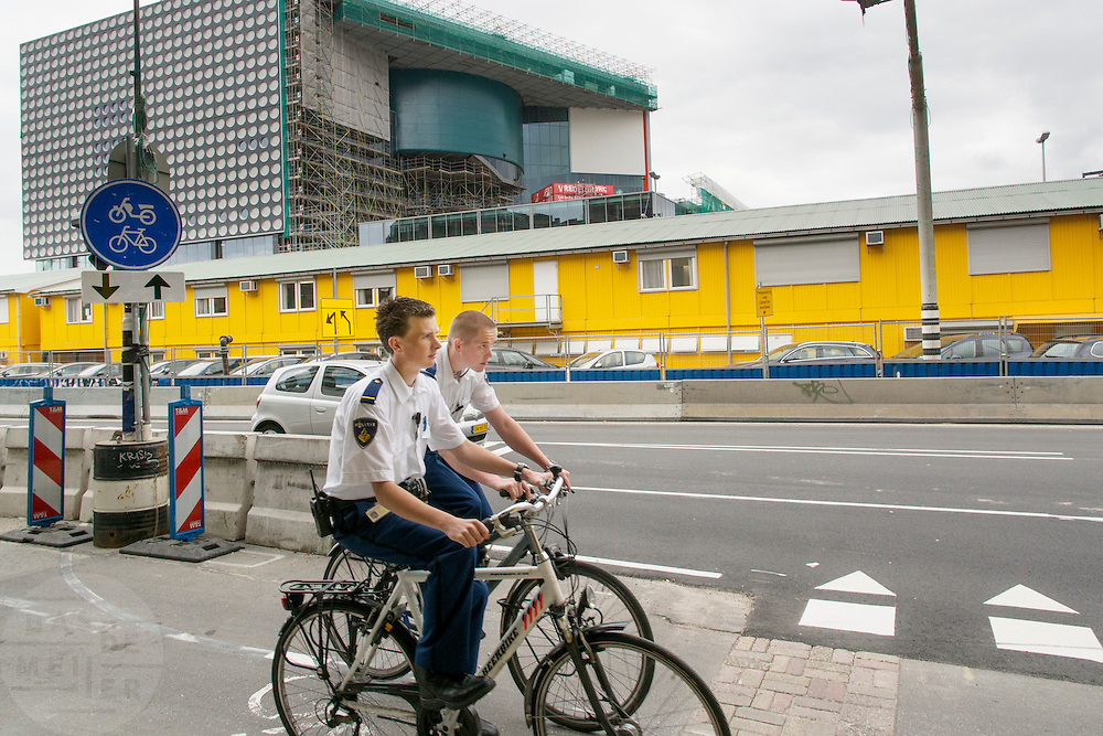 In Utrecht fietsen twee jonge agenten door het stationsgebied. In de achtergrond staat het nieuwe muziekpaleis Vredenburg dat bijna klaar is.<br /> <br /> In Utrecht two young policemen are cycling in the stations area. In the background is the new music center Vredenburg  that is almost finished.