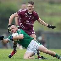 Kilmurry Ibrickane's Steven Moloney goes down after a tackle by Lissycasey's Oisin Hanrahan