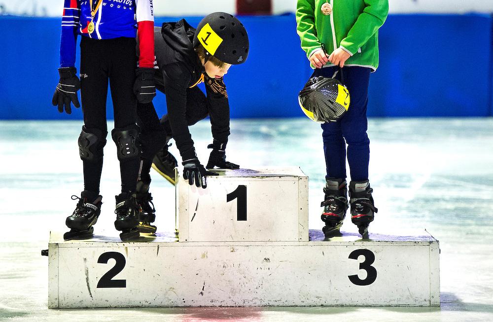 Serie ROOKIE<br /> Nederland, Leiden, 07-03-2015.<br /> Short Track.<br /> Arie Ravensbergen Bokaal 2015<br /> De jonge winnaar van de categorie schaatsklas is nog niet groot genoeg om op de hoogste trede te stappen en moet klimmen om zijn medaille te krijgen na zijn winst tijdens de Arie Ravensbergen Bokaal 2015.<br /> Foto : Klaas Jan van der Weij